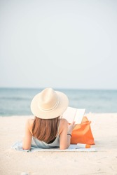 A beautiful young Asian woman enjoy reading the book on the beach. Concept for lifestyle of working woman.