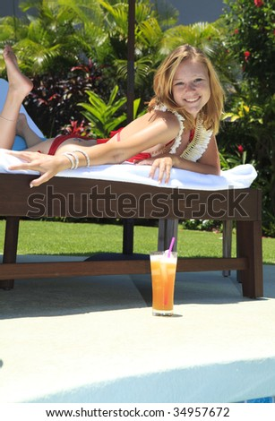 A beautiful young blond girl in a red bikini and a ginger flower lei lounges poolside in Hawaii with a tropical drink