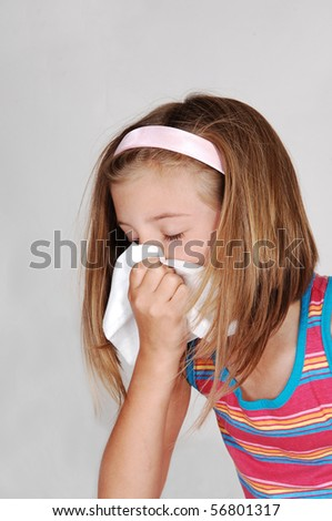 A beautiful young blond girl is sneezing in her tissue because of her cold, over light gray background. - stock photo