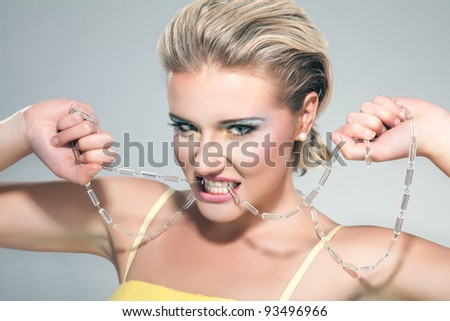 A beautiful young blond woman biting a necklace