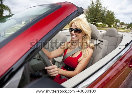 A beautiful young blond woman driving her convertible car wearing a red dress and sunglasses