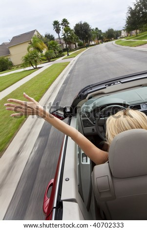 A beautiful young blond woman driving her convertible car with her hand in the air feeling the wind blowing