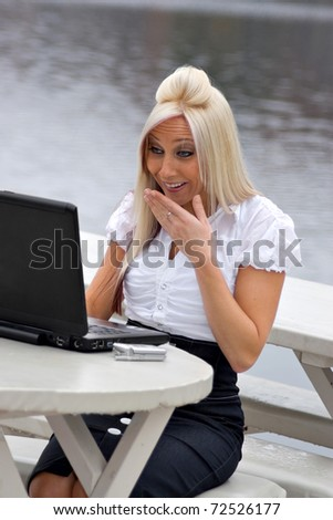 A beautiful young blond woman is shocked by what she is seeing on her social networking sites.  It looks as if she is laughing at something funny or surprising. - stock photo