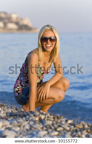 A beautiful young blond woman on a beach in the evening glow as the sun goes down