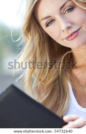 A beautiful young blond woman with stunning blue eyes reading a folder or menu