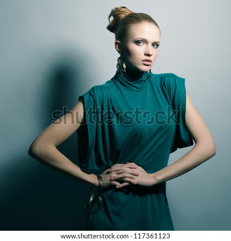 a beautiful young blonde in a green (blue) dress wearing wristbands over light blue background. studio shot