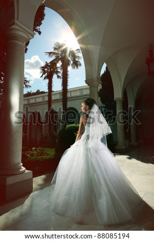 a beautiful young bride with a bouquet of flowers in the arches in a wedding dress