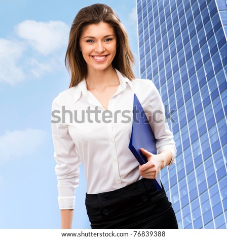 A beautiful young business woman in a field with a blue sky