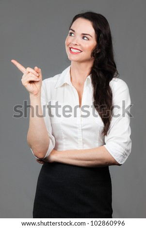A beautiful young business woman pointing and looking at copyspace, over grey background