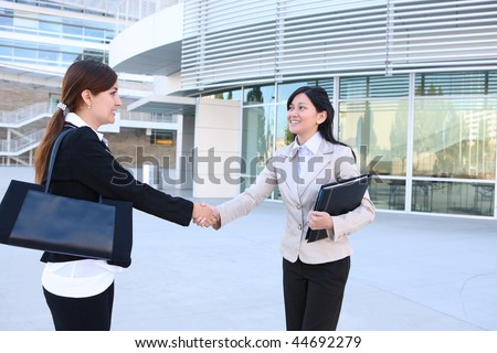A beautiful young business woman shaking hands with colleague