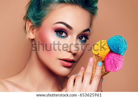 A beautiful young cheerful girl looks at him in amazement, holding a horn in her hand with a multicolored ice cream. Hairstyle - blue hair. Bright makeup. Dessert, refreshing sweetness. Bright colors.