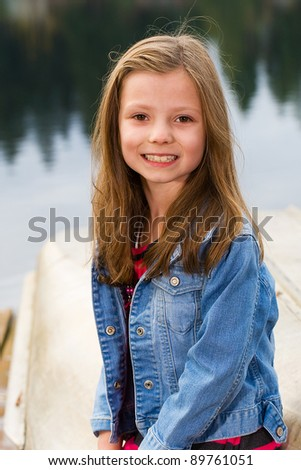 A beautiful young child with a pretty smile in a nature scene.