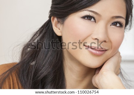 A beautiful young Chinese Asian Oriental woman resting on her hand with a wonderful smile
