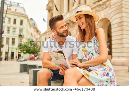 A beautiful young couple are sitting and holding a map and looking around at the Egyetem Square in Budapest, Hungary. Stock fotó ©