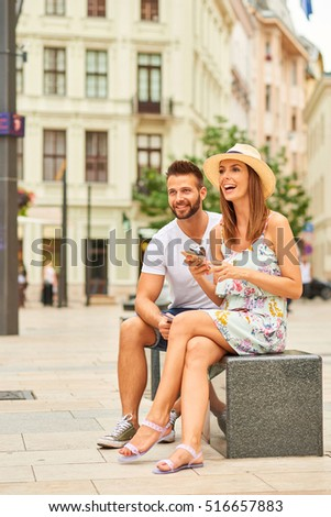 A beautiful young couple are sitting and using a smartphone at the Egyetem Square in Budapest, Hungary. Stock fotó ©