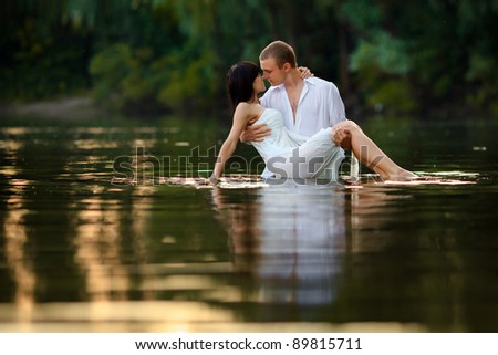 a beautiful young couple in the water - stock photo