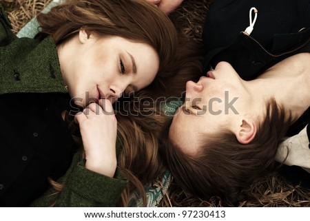 a beautiful young couple lying in the park
