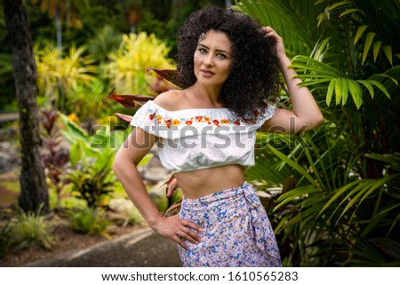 A beautiful young curly hair woman posing in the tropical garden. A half size portrait, - Portrait photography.