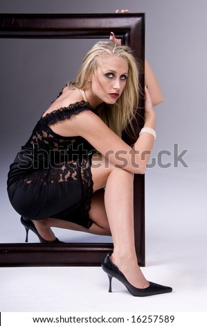 A beautiful young fashion model with long blond hair in a black cocktail dress crouched inside a picture frame - stock photo