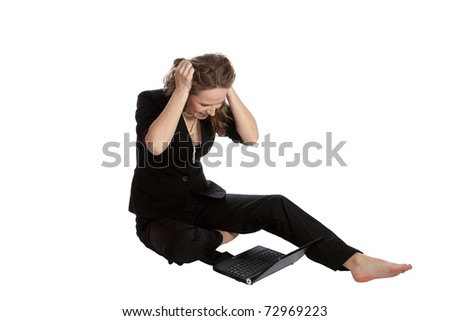 A beautiful young female executive expressing frustration at her laptop computer - stock photo