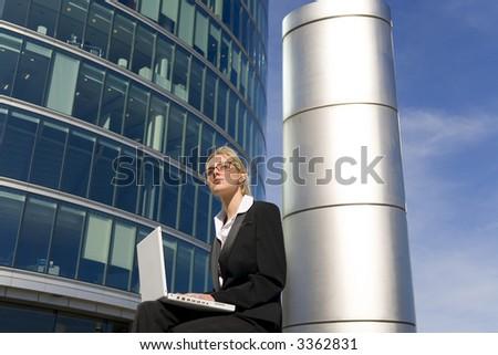 Un ejecutivo femenino joven hermoso usando su computadoraportátil en rodear urbano del hola-hi-tech