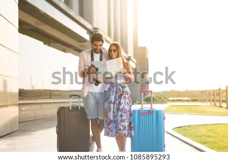 A beautiful young girl and her boyfriend are waiting to board the plane and they are looking at the map of the tourist destinations they want to visit.