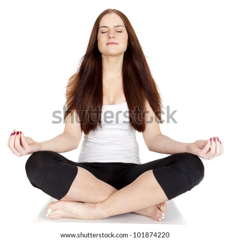 A beautiful, young girl dressed in sports clothes is sitting on the floor and meditate.