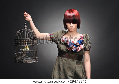 A beautiful young girl holding a birdcage with a bird inside against a dark background