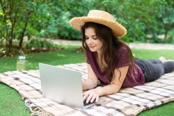 A beautiful young girl in a burgundy T-shirt and with long hair and straw hat lies on a plaid, on green grass, on the lawn and working behind a laptop. Remote work.