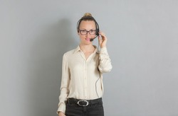 a beautiful young girl in a white silk blouse in a business-like style of clothing with an earpiece speaks into a microphone. She's a call center worker or a radio DJ.