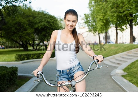 A beautiful young girl in a white T-shirt and blue jeans is riding a bicycle through the city - Outdoors