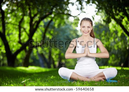 A beautiful young girl in lotus pose in the park