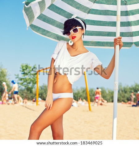 a beautiful young girl in retro look with red lips in a white swimsuit, a bandana and sunglasses is standing under the beach umbrella and is posing for the camera - stock photo