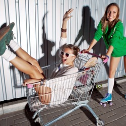 a beautiful young girl in sexy shorts and roller skates is pushing a supermarket trolley with a laughing girl. they both are projecting shadows onto the wall