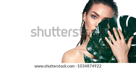 A beautiful young girl in the studio on a white background with wet skin and wet hair holds a large green tropical leaf in hands and covers a part of her face. #1034874922