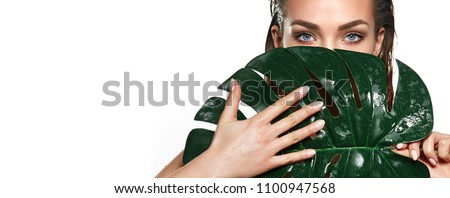 A beautiful young girl in the studio on a white background with wet skin and wet hair holds a large green tropical leaf in hands and covers a part of her face.fashion, beauty, makeup, cosmetics. #1100947568