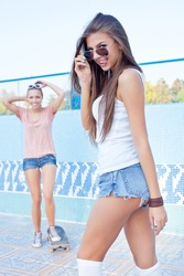 a beautiful young girl is watching the other flirting and setting the sunglasses