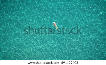 A beautiful young girl lies on a mattress in the open sea or in the pool, a pink bikini, hat, sunglasses, blue clear water, a top view. Concept: sea air, summer, travel, vacation, freedom, sun, enjoy  #691129408