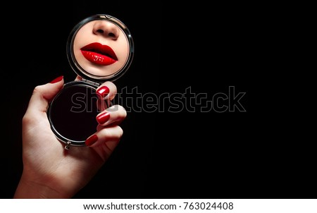 A beautiful young girl looks in the mirror and sees a reflection of red lips.Beauty, fashion, hairstyle, stylist, boutique, advertising, discounts, beauty salon, magazine.