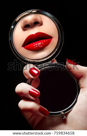 A beautiful young girl looks in the mirror and sees a reflection of red lips.fashion, beauty, advertising, beauty salon, make-up artist, cut-away, reflection, manicure, make-up, cosmetics, face.