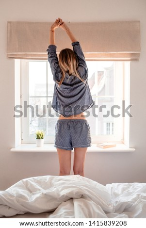 A beautiful young girl stretches against the window on a sunny morning. Morning work-out and fitness. Awakening from sleep concept. Start day of the women. Good morning, morning magic. Female relax #1415839208
