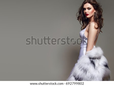 A beautiful young girl with a chic figure and long dark hair stands in the studio in a white silk dress and a fluffy white fur coat.Suite,glamor,fur salon,ode,beauty,cosmetics, make-up,beautiful hair.