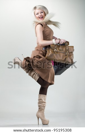 a beautiful young girl with a glamorous bag and packages in the hands of happy smiles and fun shopping