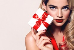A beautiful young girl with blond hair and red lips is holding a white gift box with a red ribbon.fashion, beauty, gifts, sales, festive packaging, evening dress, holiday, new year, christmas.