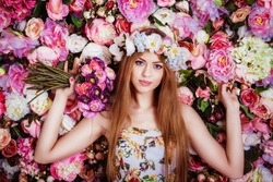 A beautiful young girl with flowers bouquet near a floral wall.