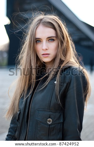 a beautiful young girl with hair fluttering in the wind in jacket