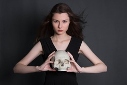 A beautiful, young girl with long hair in a black dress with a skull in her hands. Studio photo on a gray background. Witchcraft, necromancy, fortune telling, Halloween.