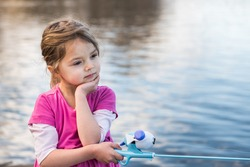 A beautiful young girls stands on a dock on the edge of a river and goes fishing with a fishing rod on a warm spring day in the evening.