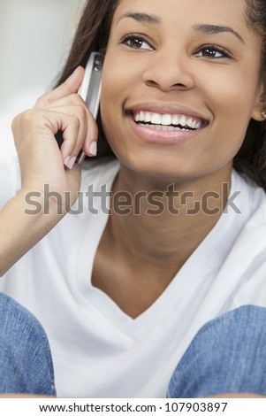 A beautiful young happy African American young woman or girl with a wonderful smile chatting on her cell phone.