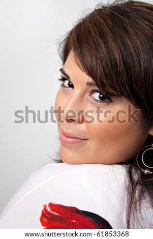 A beautiful young Hispanic woman with a smile on her face isolated over a silver background.